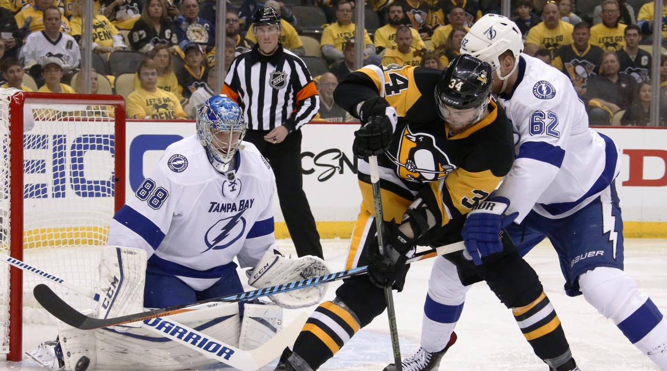 Tampa Bay Lightning goalie Andrei Vasilevskiy (88) stops the puck as Pittsburgh Penguins' Tom Kuhnhackl (34) and Lightning's Andrej Sustr (62) tangle in front of the net during the second period of Game 1 of the NHL hockey Stanley Cup Eastern Conference f