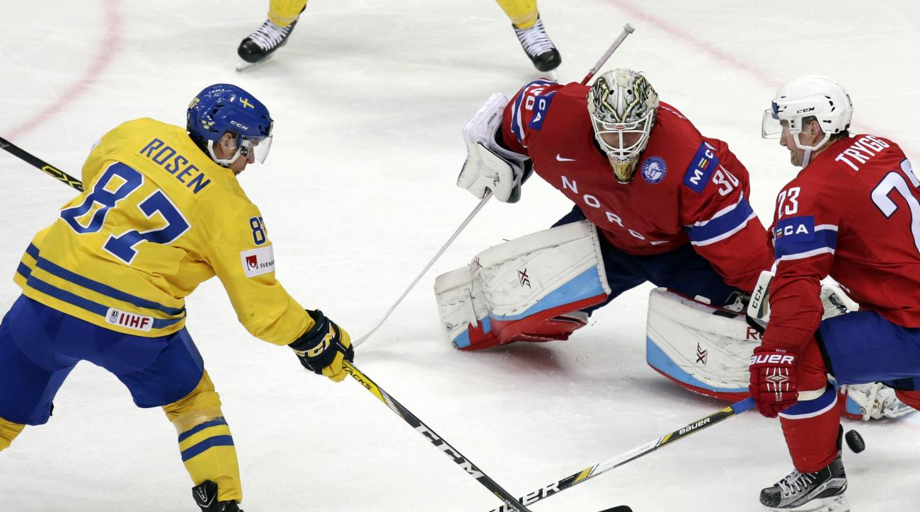 Swedens Robert Rosen, left, scores a goal past Norways goalie Lars Haugen, center, during the Ice Hockey World Championships Group A match between Norway and Sweden, in Moscow, Russia, on Saturday, May 14, 2016. (AP Photo/Pavel Golovkin)