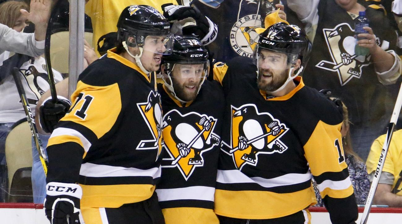 Pittsburgh Penguins' Bryan Rust, center is congratulated by teammates Evgeni Malkin, left, and Ben Lovejoy (12) after scoring against the Tampa Bay Lightning during the second period of Game 7 of the NHL hockey Stanley Cup Eastern Conference finals, Thurs