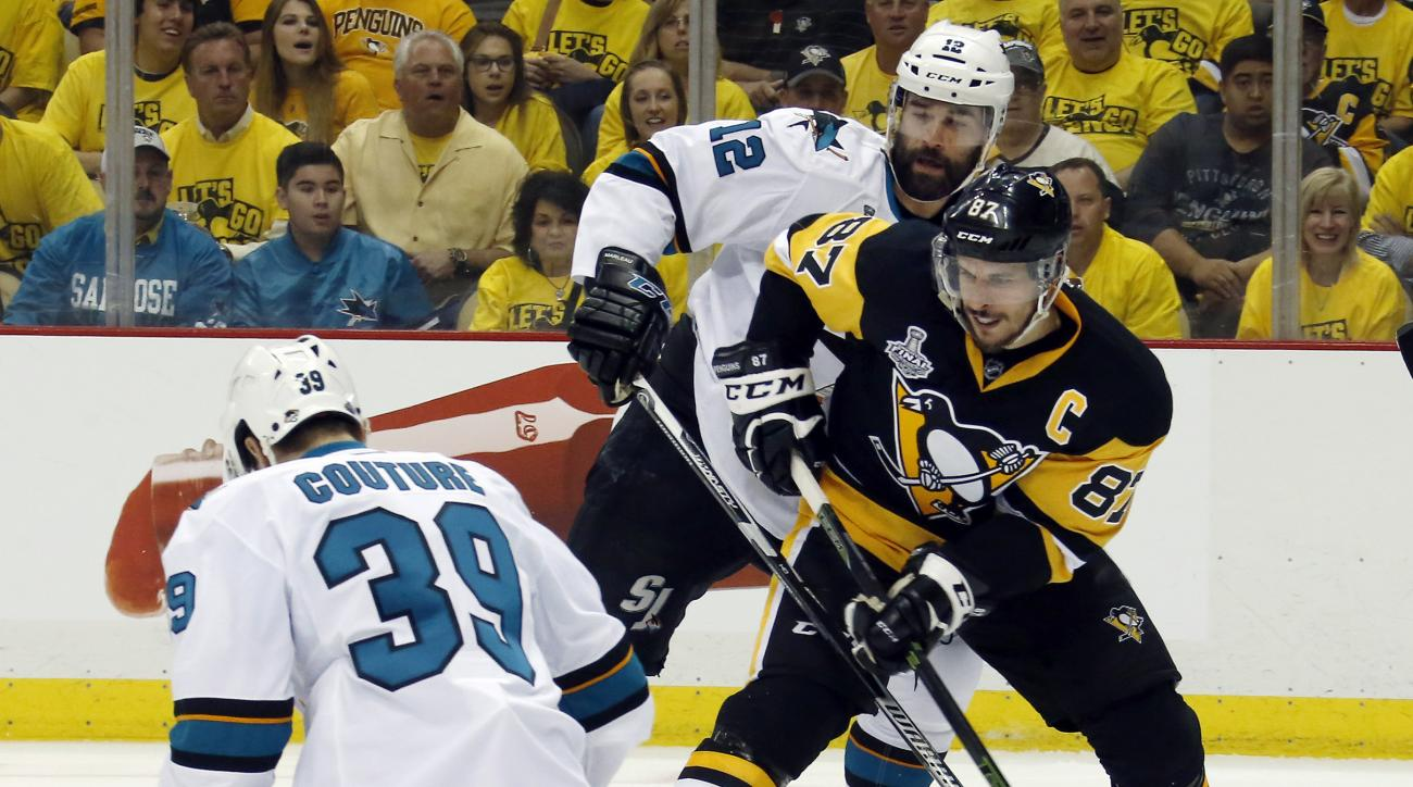 Pittsburgh Penguins' Sidney Crosby (87) tries to pass against San Jose Sharks' Logan Couture (39) and Patrick Marleau (12) during the first period of Game 1 of the Stanley Cup final series Monday, May 30, 2016, in Pittsburgh. (AP Photo/Keith Srakocic)