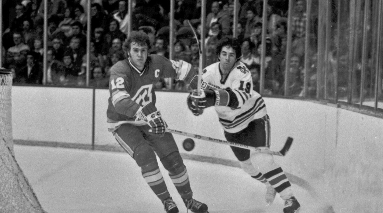 FILE - In this Dec. 18, 1977, file photo, Atlanta Flames' Tom Lysiak, left, and Chicago Blackhawks' Dale Tallon chase after the puck during the first period of an NHL hockey game in Chicago. Lysiak, a three-time NHL All-Star who played 13 NHL seasons with