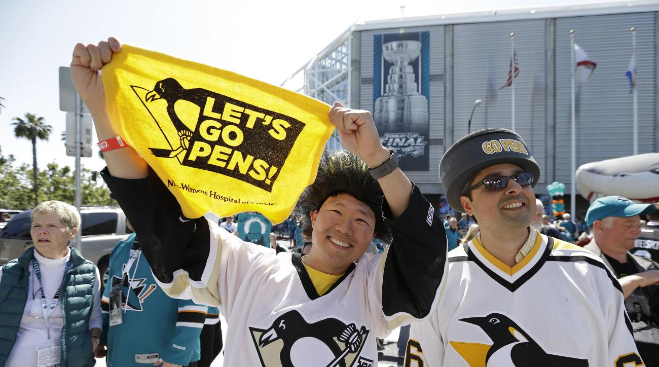 Thad Hwang, left, and Angelo Puglisi, right, both of San Francisco, watch a live broadcast outside SAP Center before the start of Game 4 of the NHL hockey Stanley Cup Finals between the San Jose Sharks and Pittsburgh Penguins in San Jose, Calif., Monday,