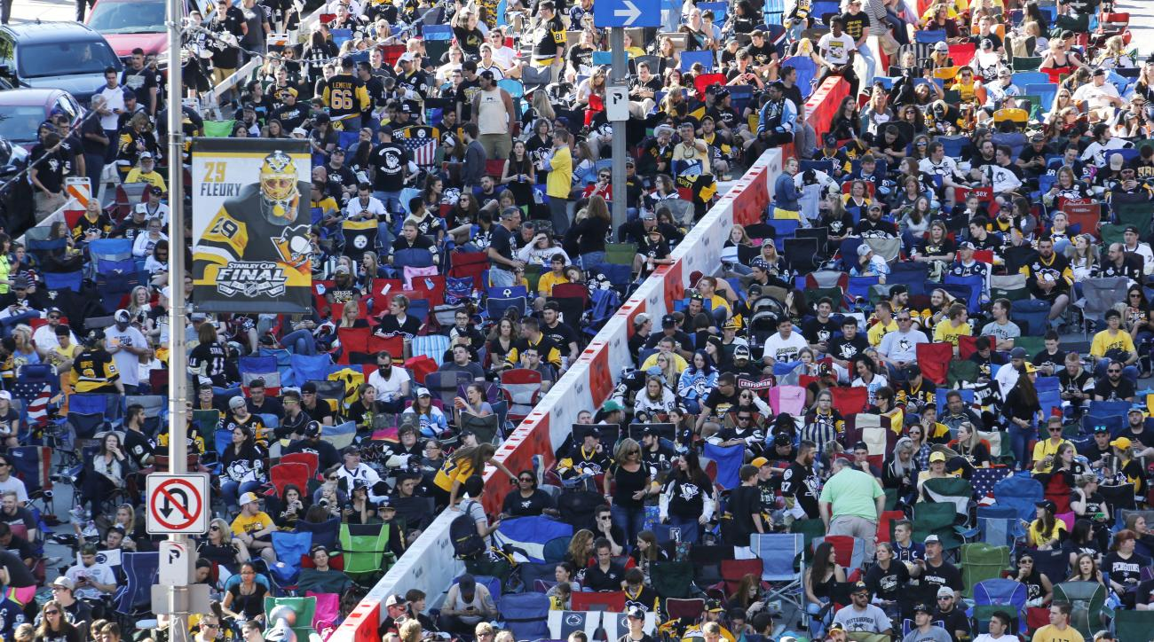 A throng of fans gather in the fan zone to watch Game 5 of the NHL hockey Stanley Cup Finals between the Pittsburgh Penguins and the San Jose Sharks on a big screen in front of the Consol Energy Center, Thursday, June 9, 2016, in Pittsburgh. (AP Photo/Gen