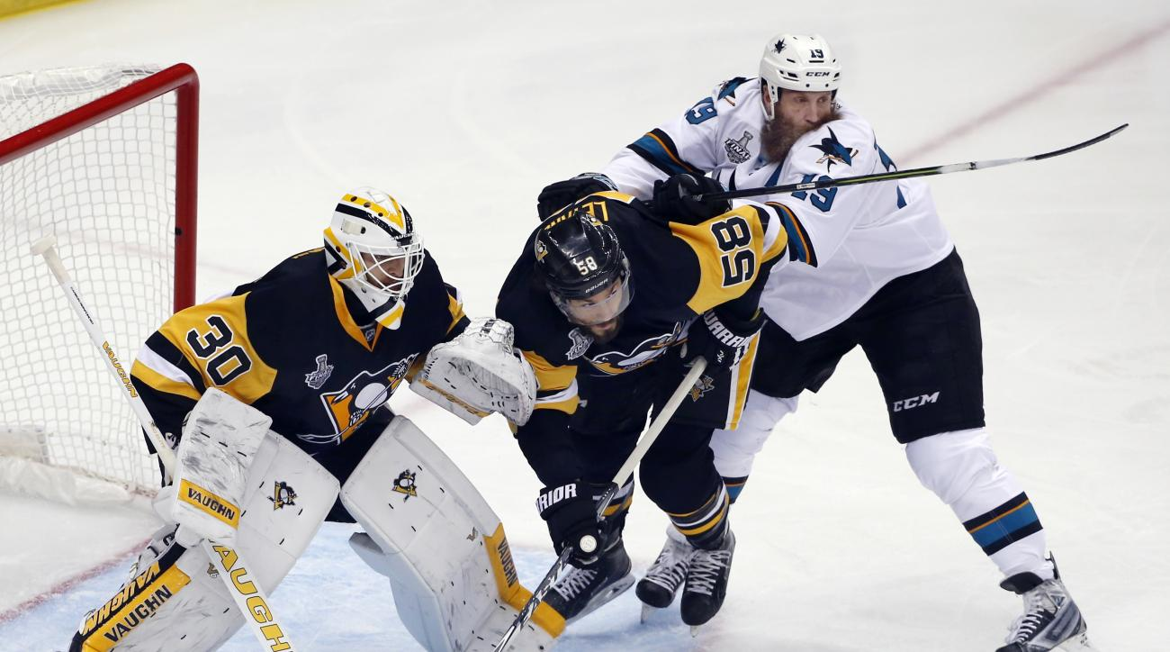 San Jose Sharks' Joe Thornton (19) checks Pittsburgh Penguins' Kris Letang (58) in front of Penguins goalie Matt Murray (30) during the first period in Game 5 of the NHL hockey Stanley Cup Finals on Thursday, June 9, 2016, in Pittsburgh. (AP Photo/Gene J.