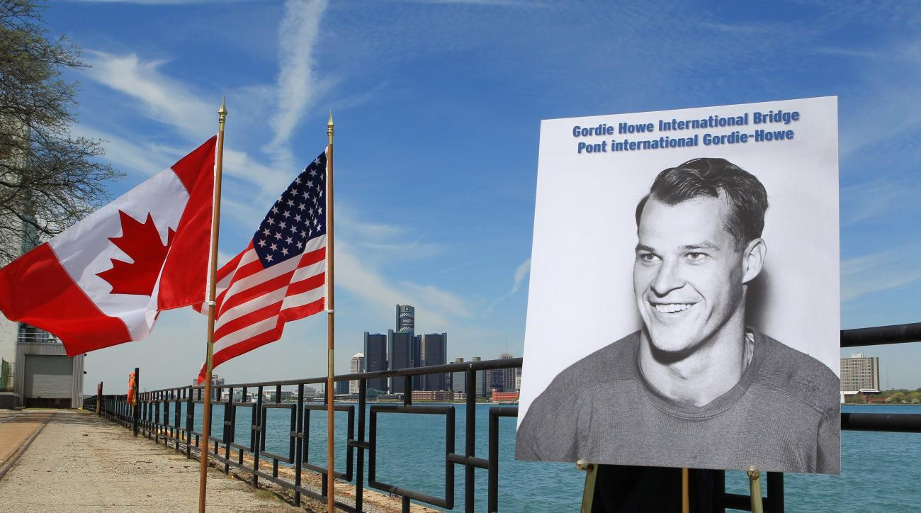 FILE - In this May 14, 2015, file photo, a photograph of Gordie Howe is displayed on the riverfront after a news conference in Windsor, Ontario, announcing that a planned bridge connecting Detroit, rear, and Windsor, will be named after the hockey Hall of