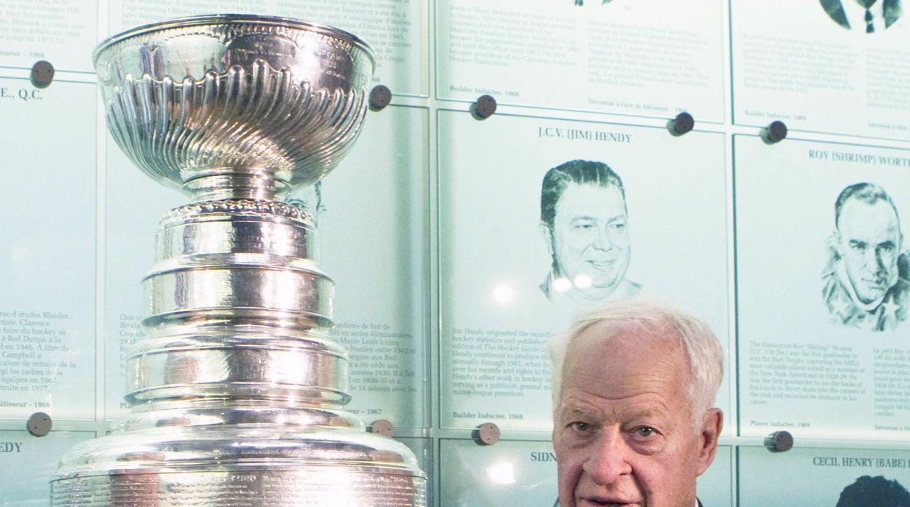 FILE - In this Nov. 14, 2011, file photo, Hockey Hall of Famer Gordie Howe poses beside the Stanley Cup at the Hall of Fame in Toronto. Howe, the rough-and-tumble Canadian farm boy whose boundless blend of talent and toughness made him the NHLs quintessen