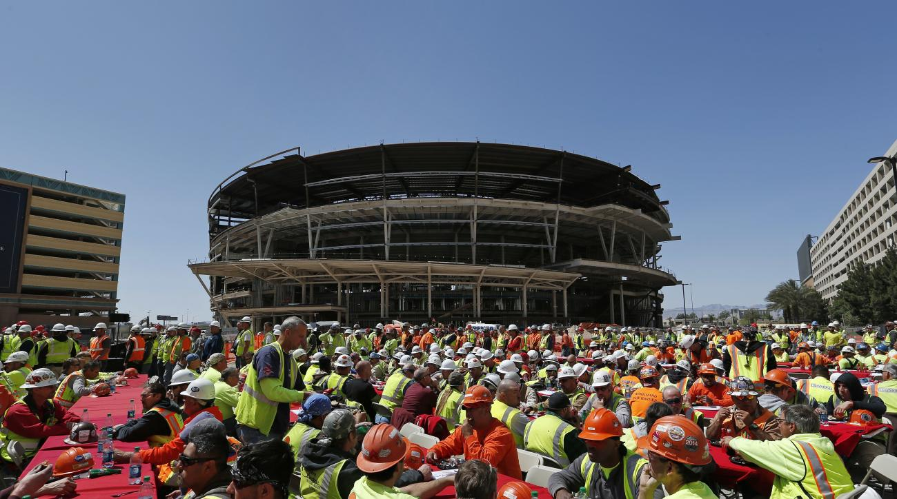 FILE - In this April 7, 2015, file photo, construction workers eat lunch by an MGM arena being built behind the New York-New York casino-hotel in Las Vegas. Hockey fans and civic boosters are getting excited at the prospect of the NHL coming to Las Vegas.