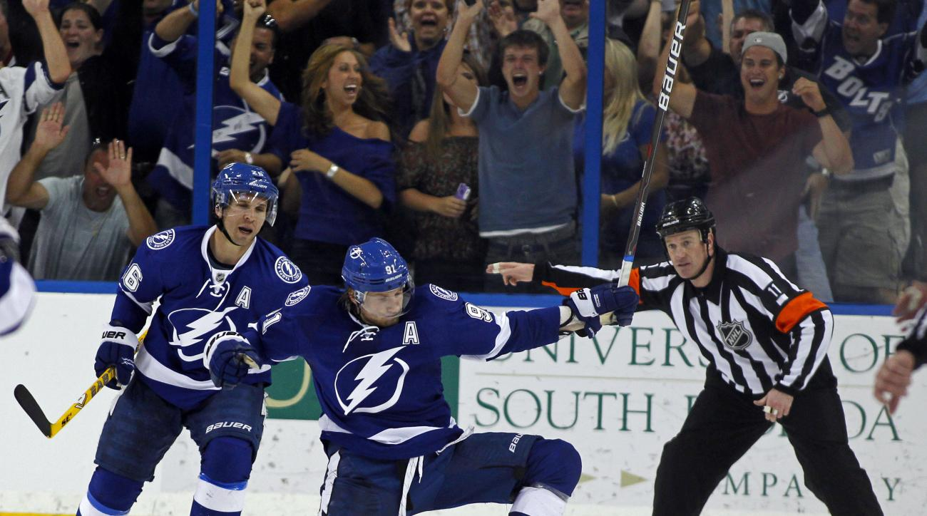 FILE - In this April 2, 2012, file photo, Tampa Bay Lightning's Steven Stamkos, center, celebrates with teammate Martin St. Louis as referee Kelly Sutherland signals Stamkos' goal during the third period of an NHL hockey game against the Washington Capita