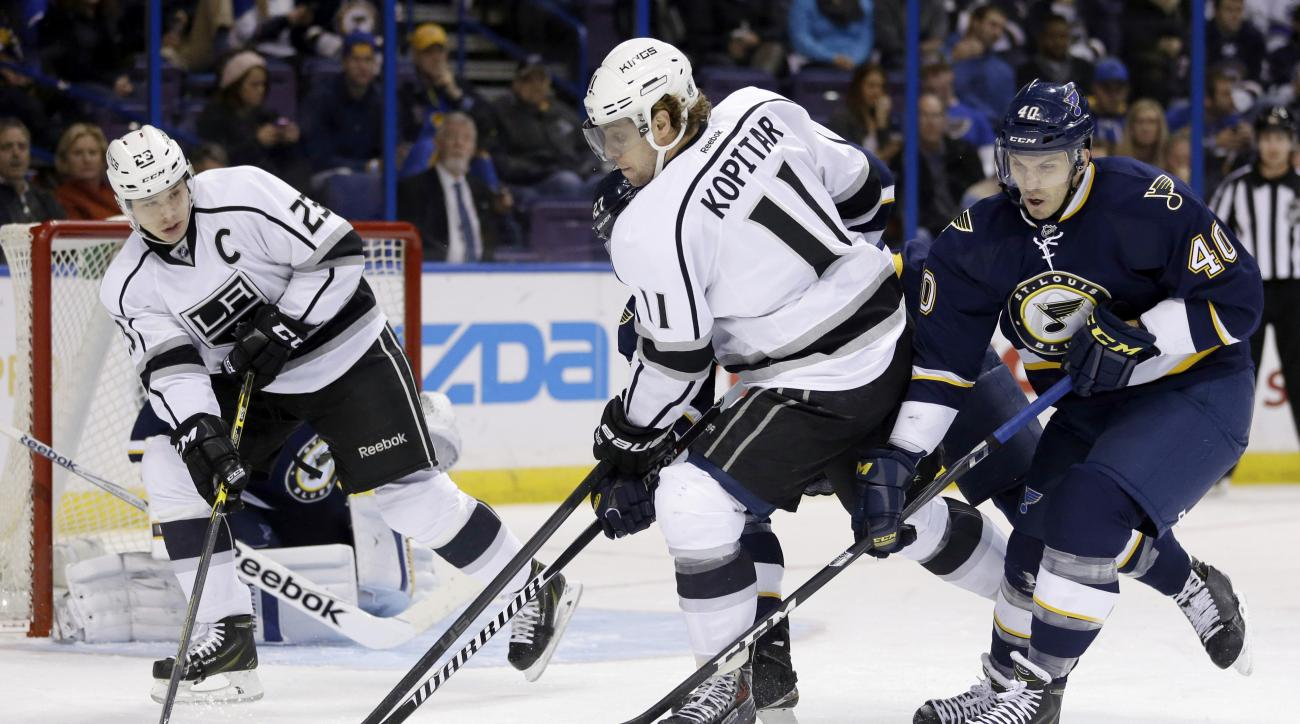 FILE - In this Dec. 16, 2014, file photo, St. Louis Blues' Maxim Lapierre, right, and Los Angeles Kings' Anze Kopitar chase a loose puck as Kings' Dustin Brown, left, watches during an NHL hockey game in St. Louis. Brown doesn't agree with the Kings' deci