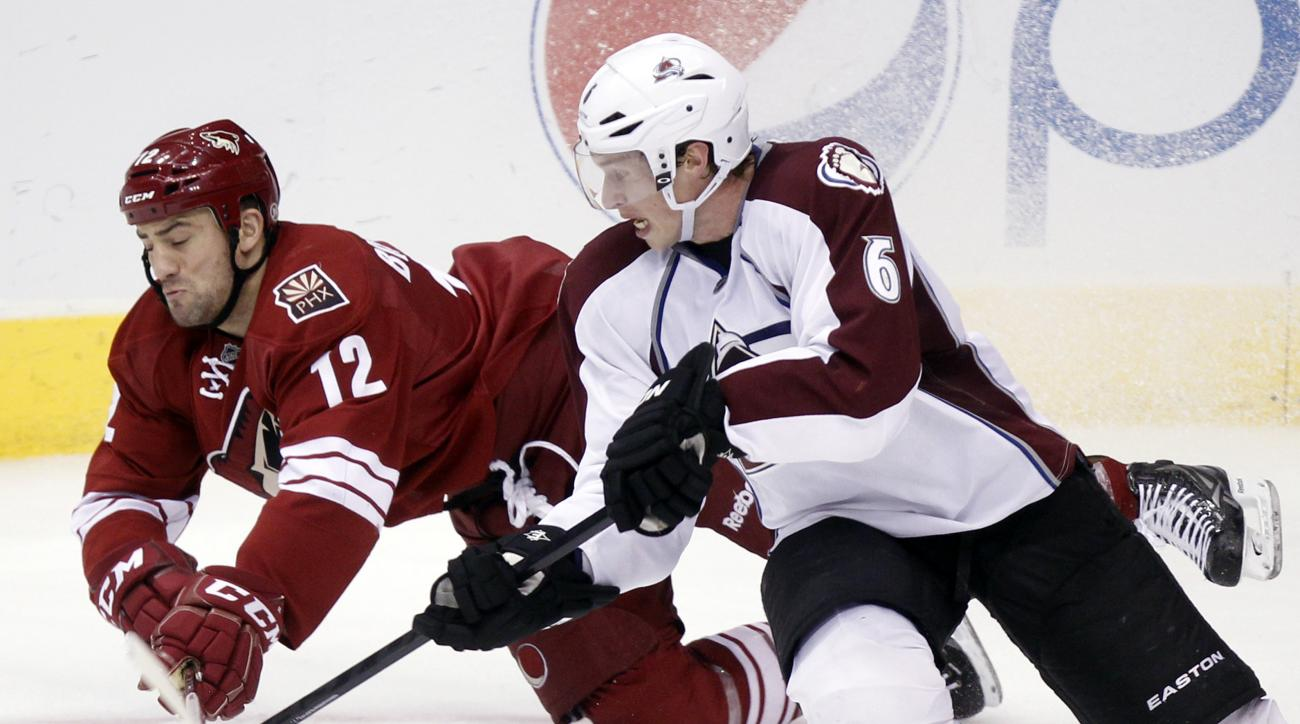 FILE - In this April 6, 2013, file photo, Phoenix Coyotes left winger Paul Bissonnette, left, and Colorado Avalanche defenseman Erik Johnson, right, compete for the puck in the third period of an NHL hockey game in Glendale, Ariz. Bissonnettes fists and f
