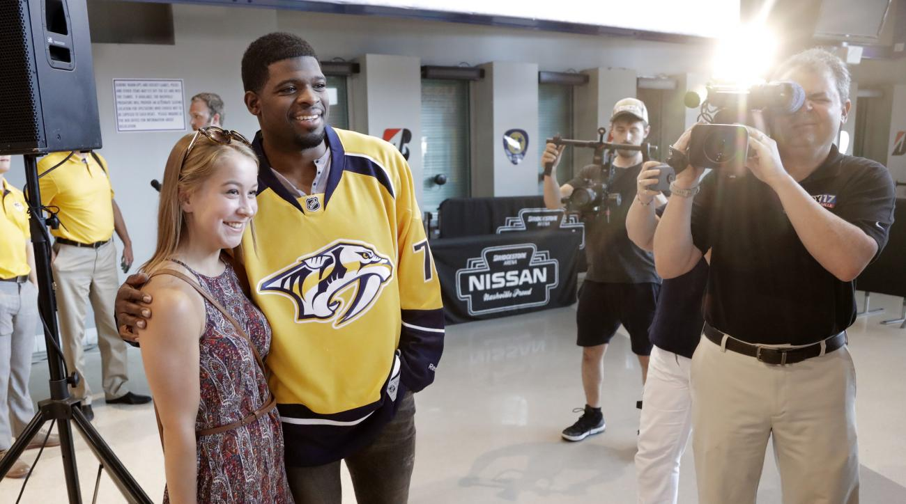 Nashville Predators defenseman P.K. Subban, second from left, poses for photos with fans after speaking at a news conference Monday, July 18, 2016, in Nashville, Tenn. Subban was acquired from the Montreal Canadiens in a trade for defenseman Shea Weber in
