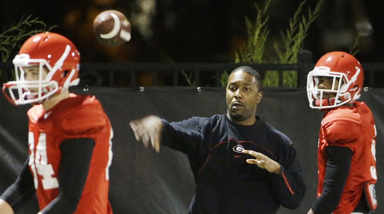 FILE- In this Dec. 16, 2015, file photo, Georgia's interim head coach Bryan McClendon, center, runs a drill during NCAA college football game in Athens, Ga. Despite having an interim coach, Georgia insists it has plenty of motivation against Penn State in