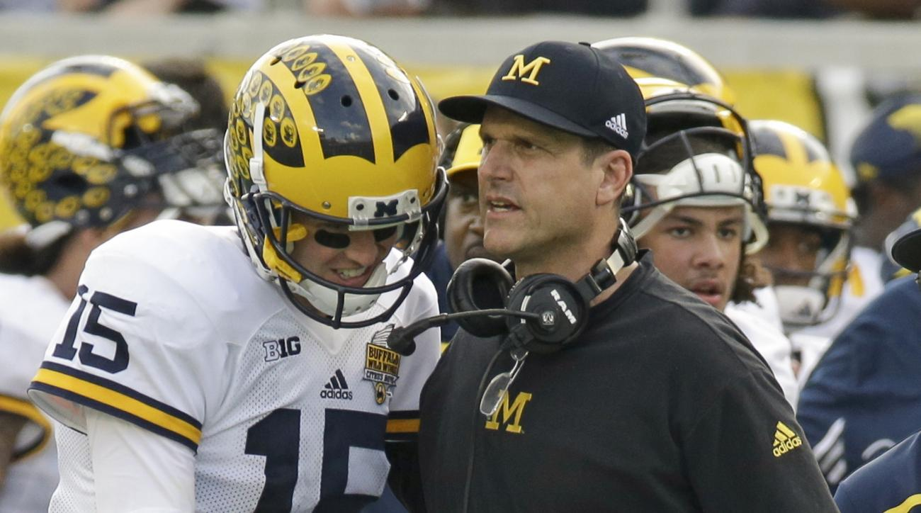 Michigan quarterback Jake Rudock (15) talks with head coach Jim Harbaugh during the final moments of the Citrus Bowl NCAA college football game against Florida, Friday, Jan. 1, 2016, in Orlando, Fla.  Michigan won 41-7. (AP Photo/John Raoux)