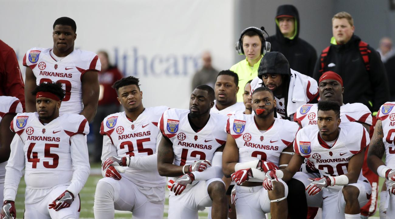 Arkansas players kneel as Arkansas wide receiver Dominique Reed, not shown, is tended to after being injured in the first half of the Liberty Bowl NCAA college football game against Kansas State Saturday, Jan. 2, 2016, in Memphis, Tenn. Reed was taken off