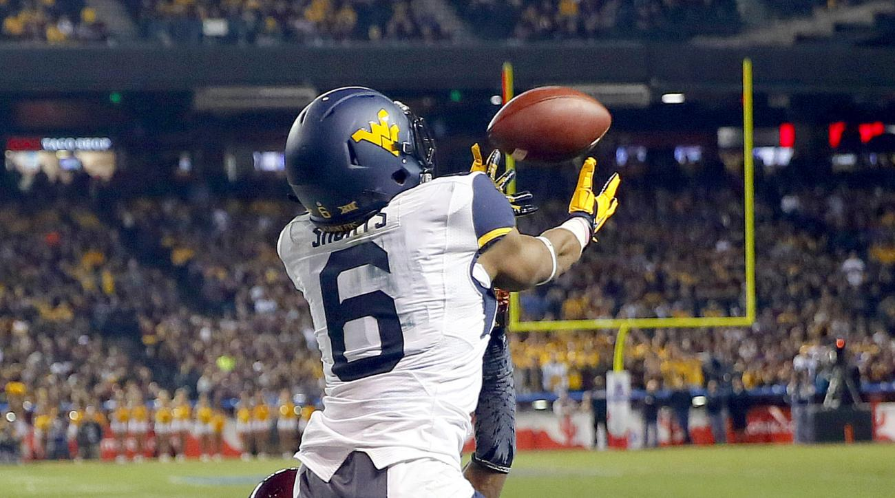 West Virginia wide receiver Daikiel Shorts (6) pulls in a touchdown catch as Arizona State defensive back Solomon Means (7) defends during the second half of the Cactus Bowl NCAA college football game, Saturday, Jan. 2, 2016, in Phoenix. (AP Photo/Matt Yo