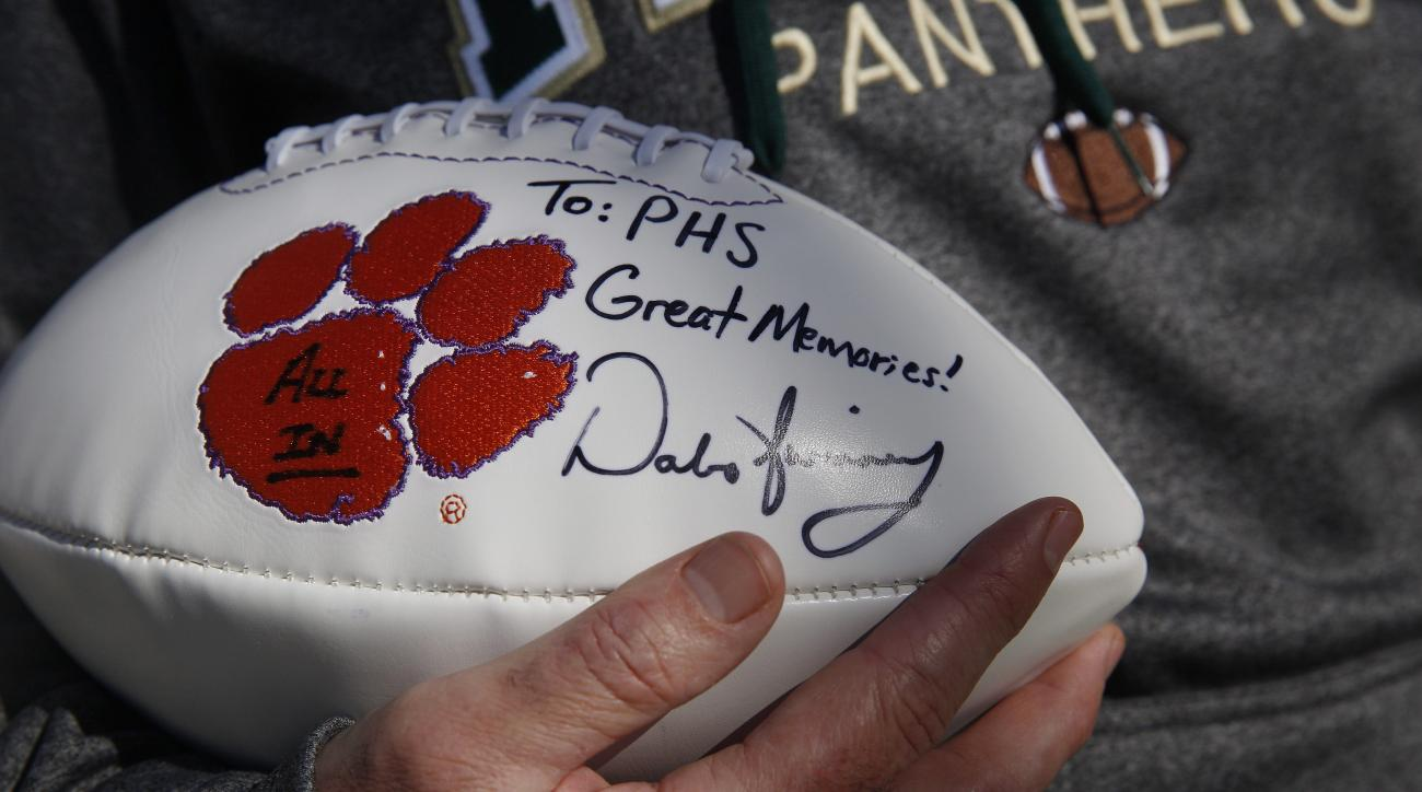 In this Tuesday, Jan. 5, 2016, photo, Pelham High School head coach Tom Causey stands outside of his office holding a football that was given to him and signed by Clemson football head coach Dabo Swinney, who attended Pelham High School, in Pelham, Ala. S
