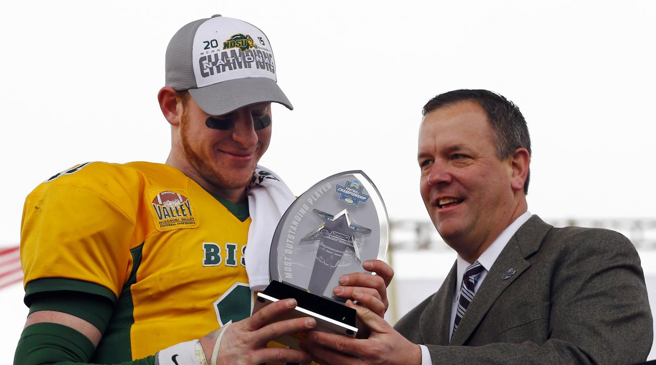 North Dakota State quarterback Carson Wentz accepts the trophy for the most valuable player after the FCS championship NCAA college football game, Saturday, Jan. 9, 2016, in Frisco, Texas.  North Dakota State beat Jacksonville State 37-10 to win their fif
