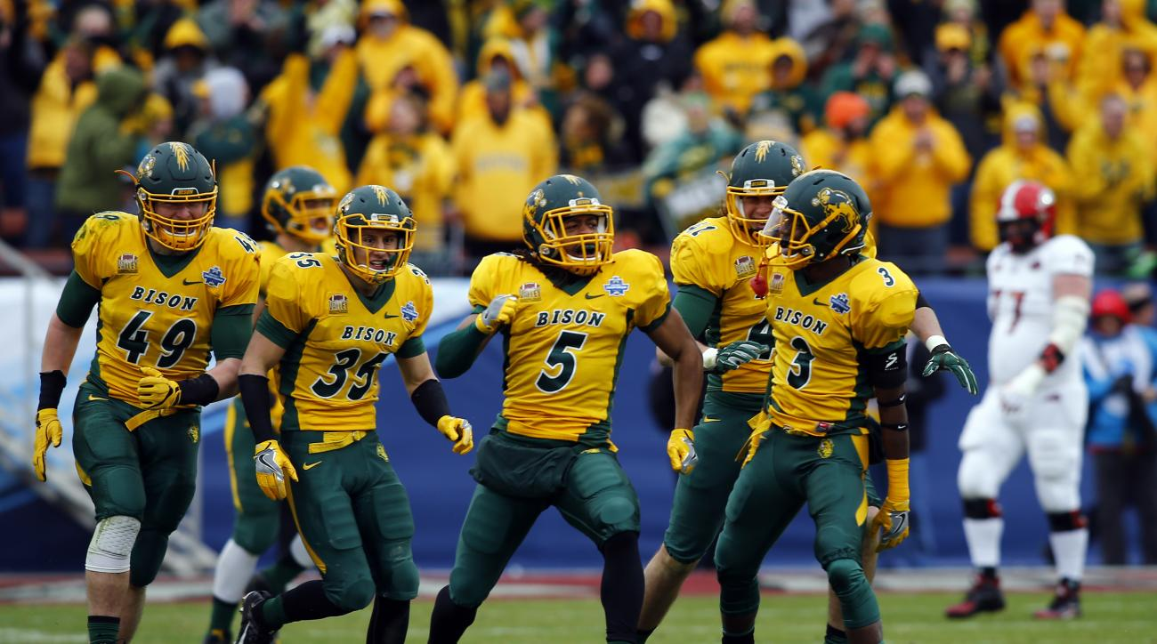 North Dakota State cornerback Jordan Champion (5) celebrates with linebacker Nick DeLuca (49), safety Robbie Grimsley (35) and safety Tre Dempsey (3) after intercepting a pass against Jacksonville State after the FCS championship NCAA college football gam