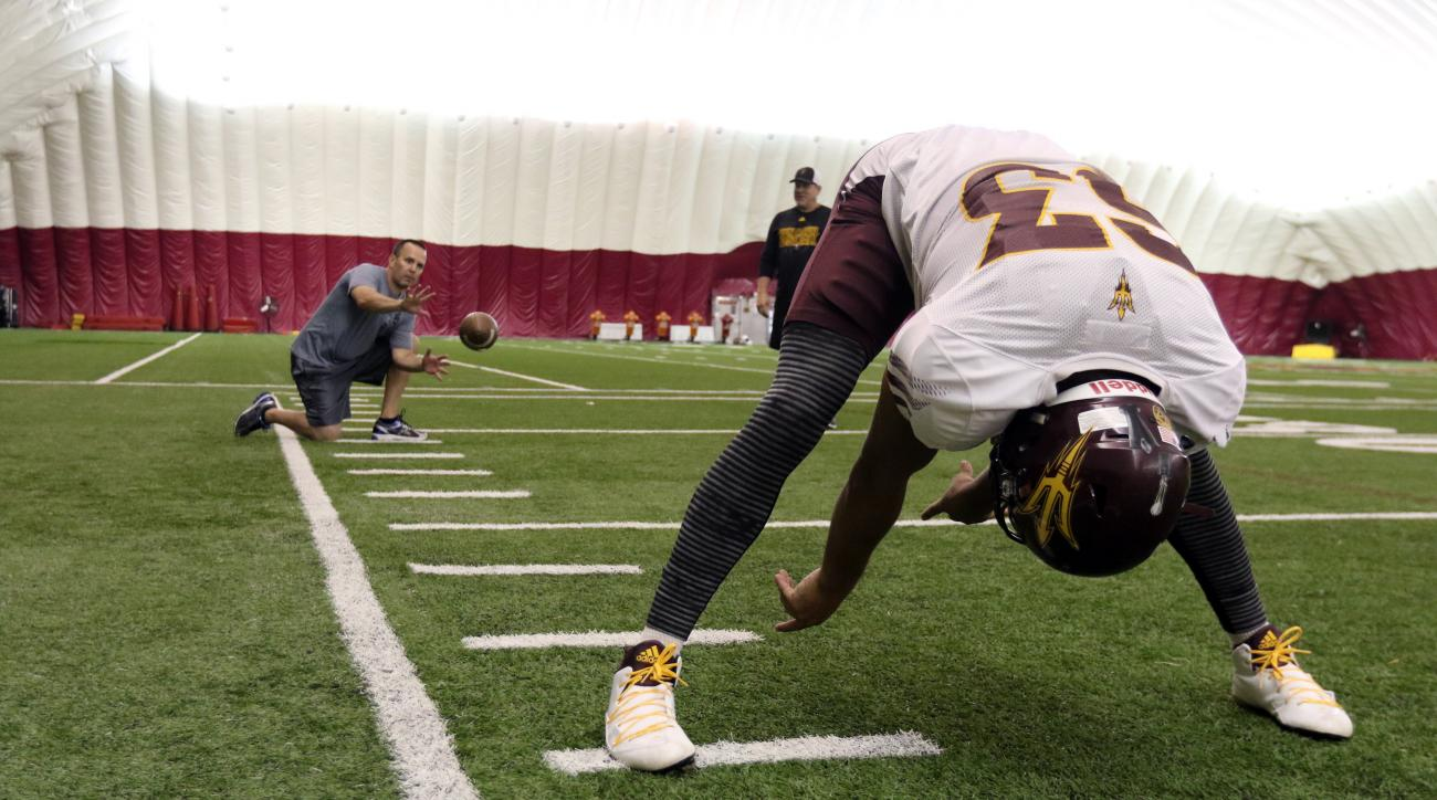 In this photo provided by Steve Rodriguez, Arizona State long snapper Mitchell Fraboni, foreground, snaps the ball to Associated Press writer John Marshall, left, as associate head coach and special teams coordinator Shawn Slocum watches Monday, Sept. 7,