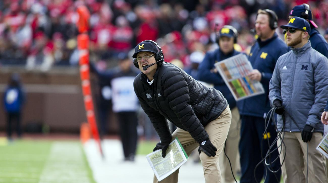 FILE - In this Nov. 28, 2015, file photo, Michigan head coach Jim Harbaugh looks up at the scoreboard in the fourth quarter of an NCAA college football game against Ohio State in Ann Arbor, Mich. Harbaugh, who has rarely shied away from the spotlight sinc