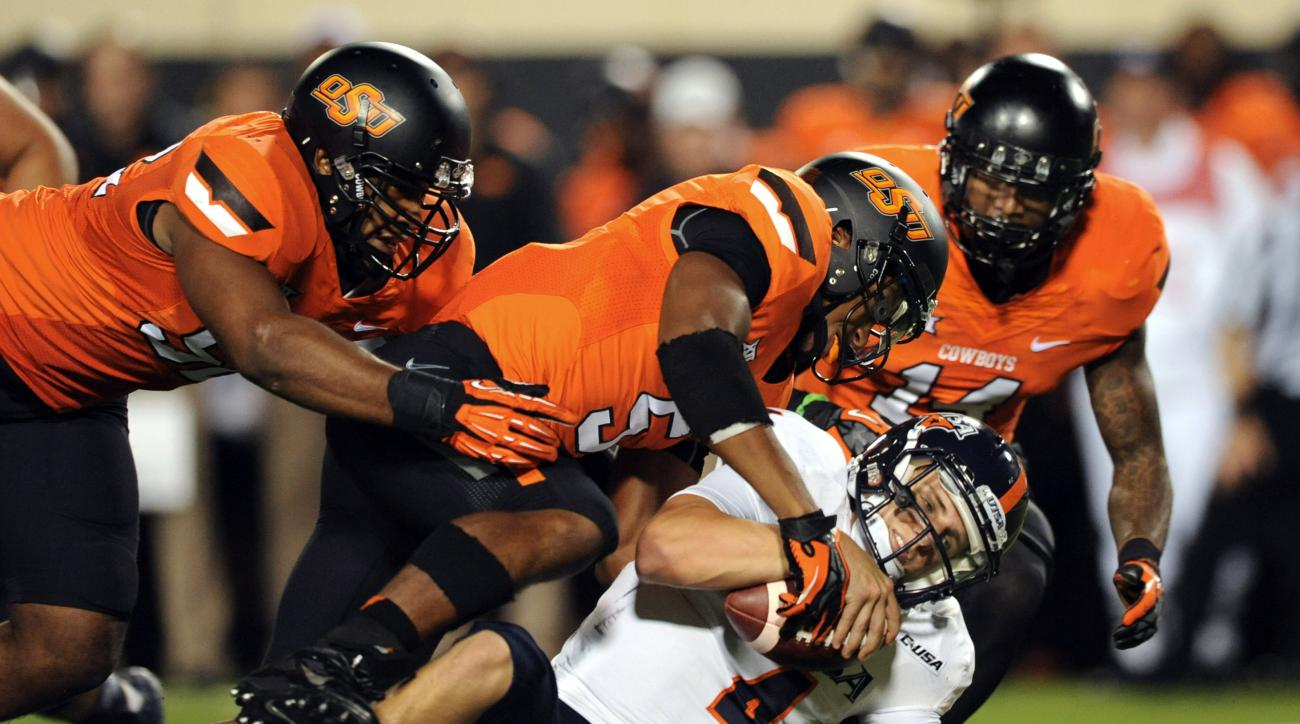 FILE - In this Sept. 13, 2014, file photo, UTSA quarterback Blake Bogenschutz, bottom, is brought to the ground by Oklahoma State's Ryan Simmons, left, Jerel Morrow, center, and Josh Furman, right, during the second half of an NCAA college football game i