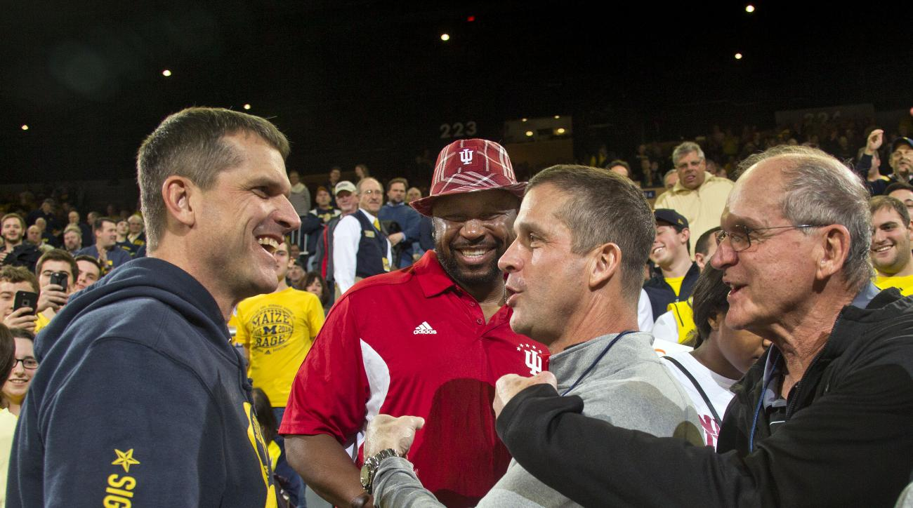 Michigan football head coach Jim Harbaugh, left, shares a laugh with Indiana guard Kevin Yogi Ferrell's father Kevin Ferrell, center left, his brother and Baltimore Ravens head coach John Harbaugh, center right, and father Jack Harbaugh, right, before an