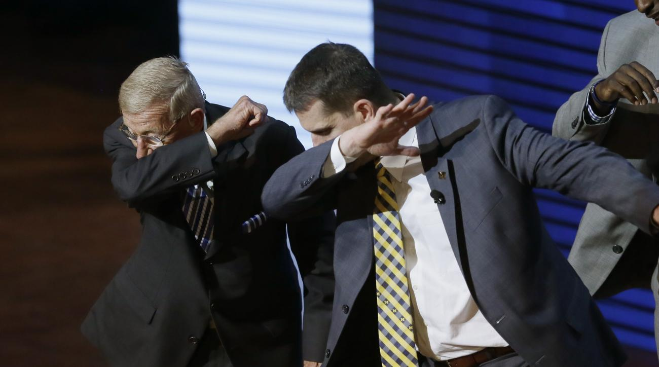 Former coach Lou Holtz, left, and University of Michigan football coach Jim Harbaugh perform a dab during the Signing With the Stars spectacle, Wednesday, Feb. 3, 2016 in Ann Arbor, Mich. Guests and superstars appeared on stage to welcome the University o