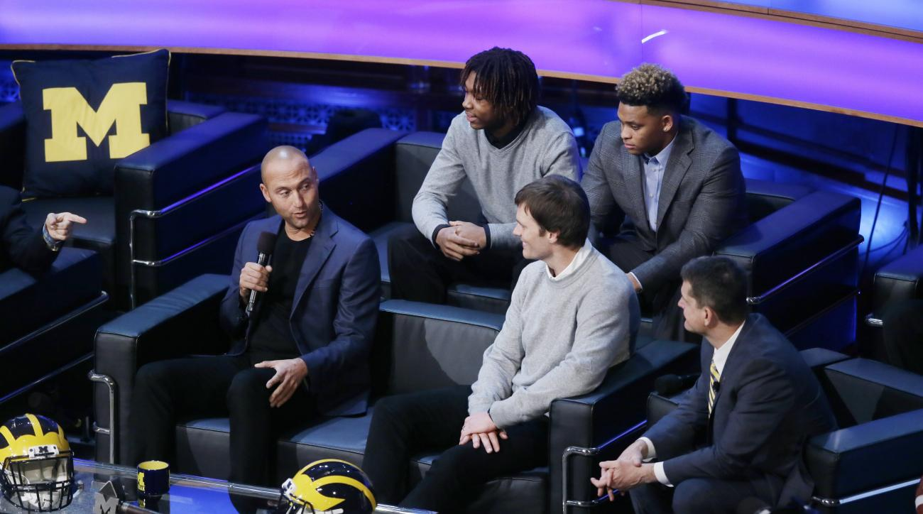 Derek Jeter, left, talks with former Michigan school quarterback Tom Brady and Michigan football coach Jim Harbaugh, right, as new recruits Kingston Davis, top right, and Ahmir Mitchell listen in, during the Signing With the Stars spectacle, Wednesday, Fe