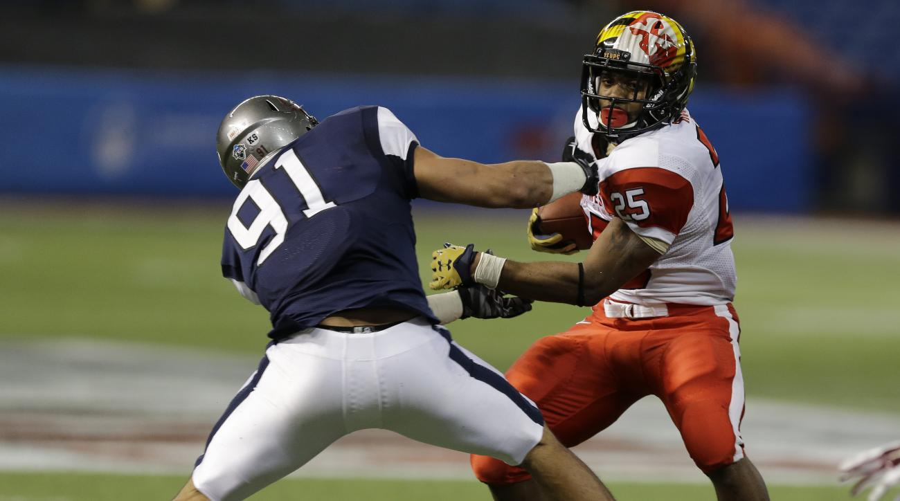 West defensive end Tyrone Holmes (91), of Montana,  stops East running back Brandon Ross (25), of Maryland, during the fourth quarter of the East West Shrine football game Saturday, Jan. 23, 2016, in St. Petersburg, Fla. (AP Photo/Chris O'Meara)