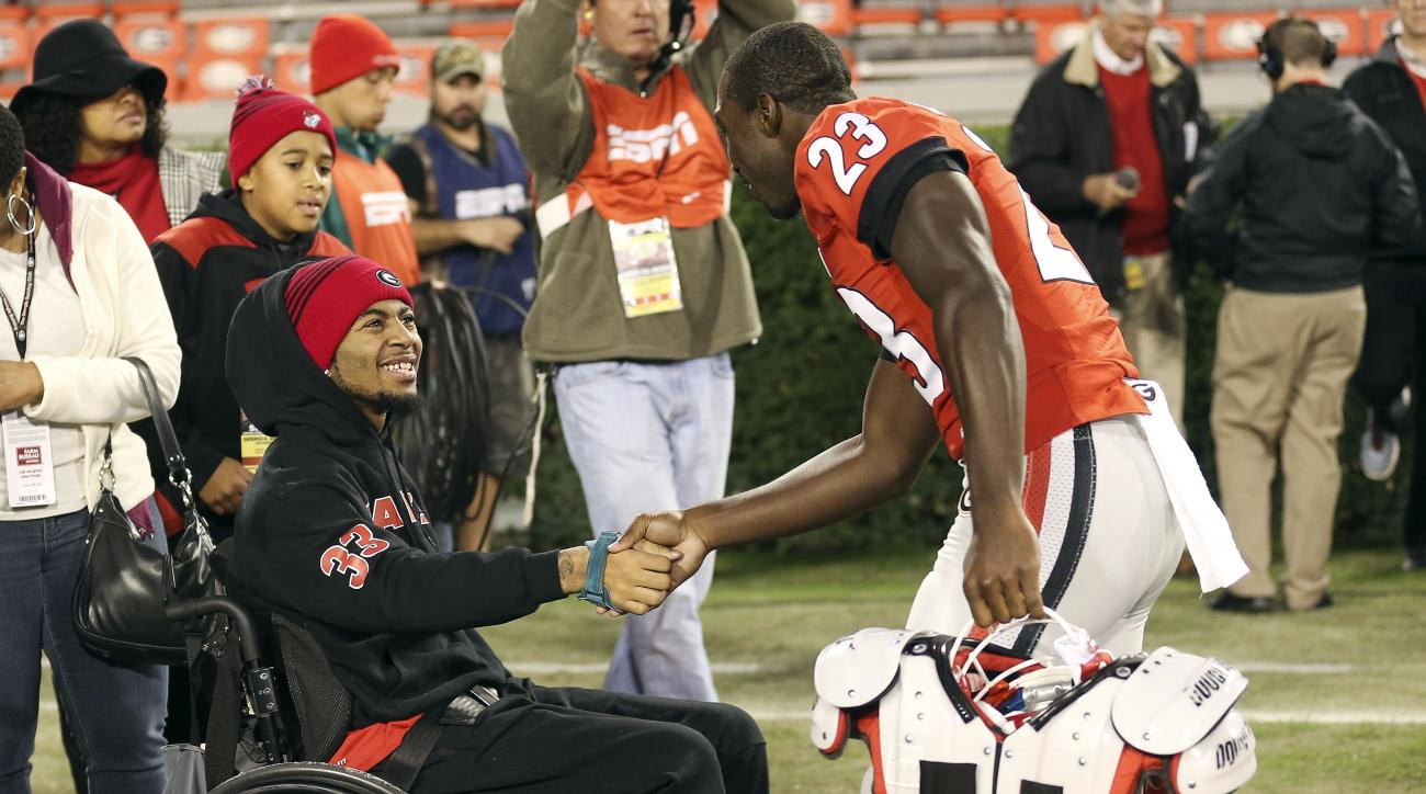FILE - In this Nov. 21, 2015, file photo, injured Southern University receiver Devon Gales is greeted by Georgia wide receiver Shakenneth Williams (23) before an NCAA college football game between Georgia and Georgia Southern, in Athens, Ga. Gales, the So
