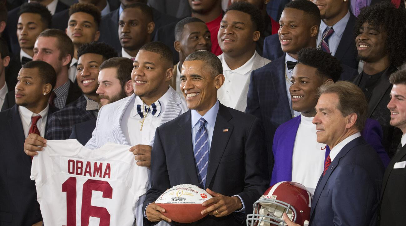 President Barack Obama holds a football for a group portrait as he honors the 2015-2016 College Football Playoff National Champion Alabama Crimson Tide football team, Wednesday, March 2, 2016, during a ceremony in the East Room of the White House in Washi