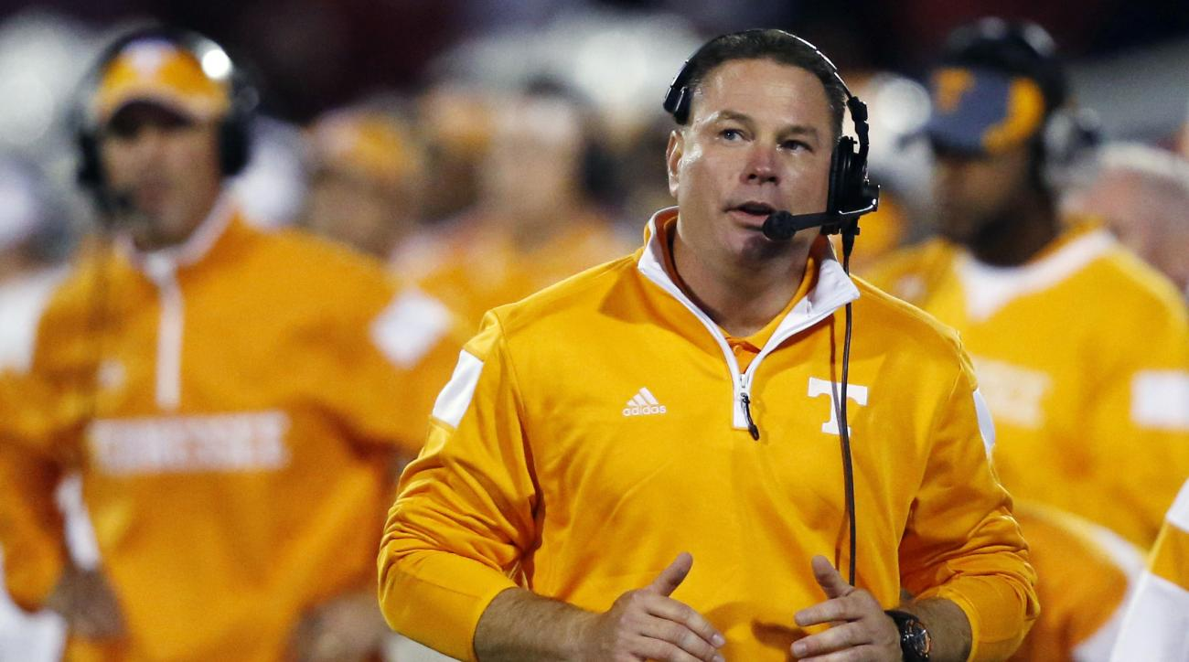 FILE - In this Saturday, Sept. 13, 2014 file photo, Tennessee coach Butch Jones talks into his microphone as he walks along the sideline in the third quarter of an NCAA college football game against Oklahoma in Norman, Okla. Tennessee football coach Butch