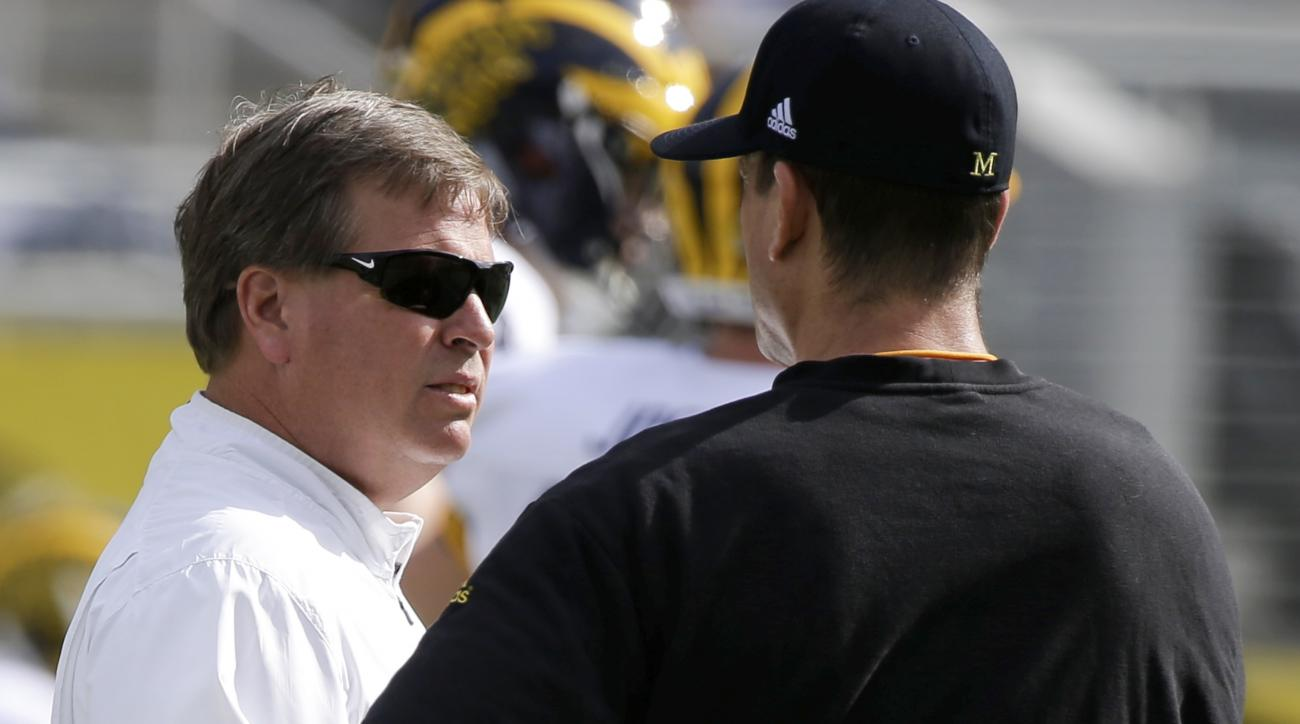 FILE - In this Jan. 1, 2016, file photo, Florida head coach Jim McElwain, left, and Michigan head coach Jim Harbaugh talk before the Citrus Bowl NCAA college football game, in Orlando, Fla. Not every Southeastern Conference coach is condemning Michigan an