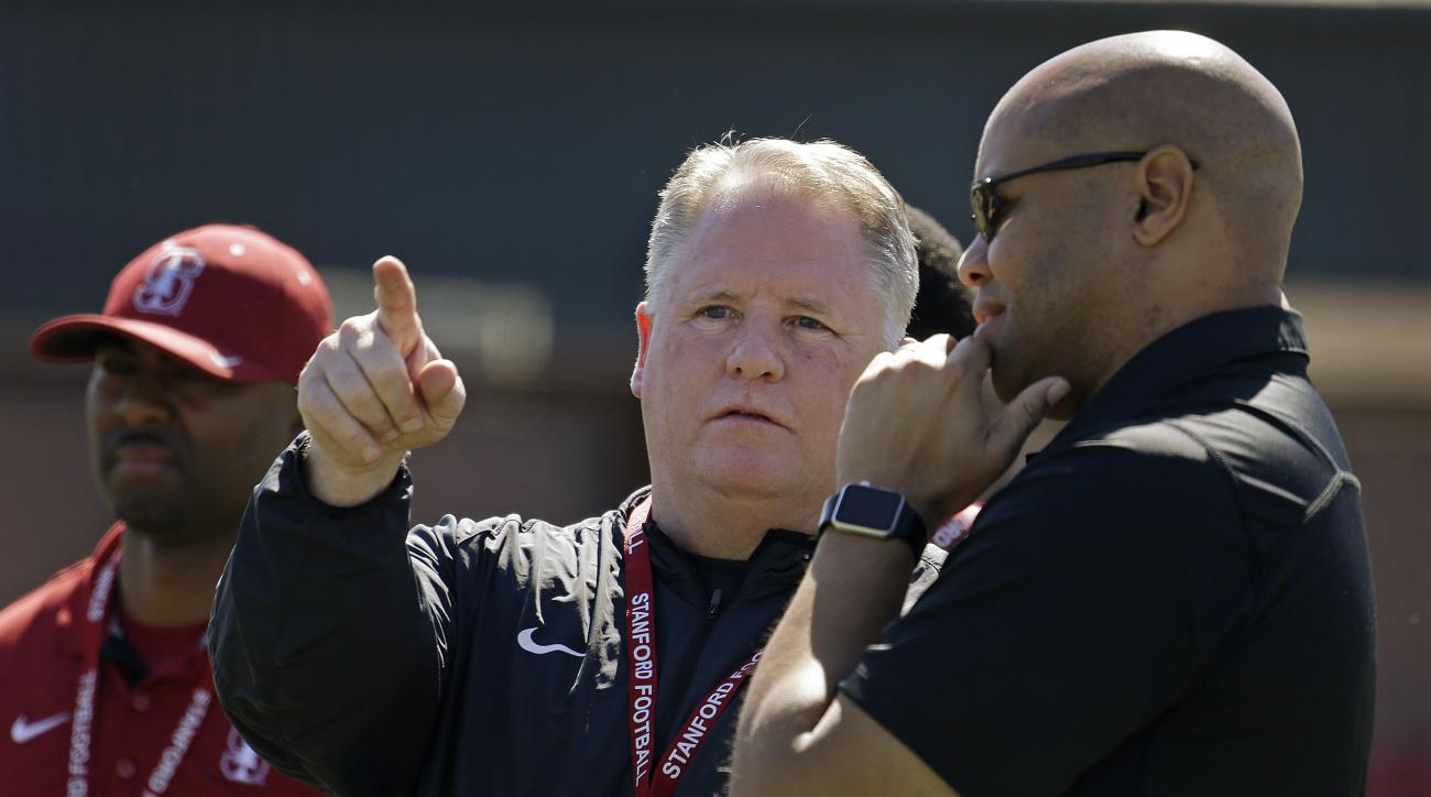 San Francisco 49ers' coach Chip Kelly, center, gestures beside Stanford football coach David Shaw, right, during Stanford's NFL Pro Day Thursday, March 17, 2016, in Stanford, Calif. (AP Photo/Ben Margot)