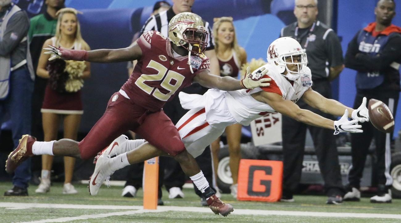 FILE - In this Dec. 15, 2015, file photo, Houston wide receiver Chance Allen (21) reaches for the ball as Florida State defensive back Nate Andrews (29) defends during the second half of the Peach Bowl NCAA college football game in Atlanta. Players on Flo