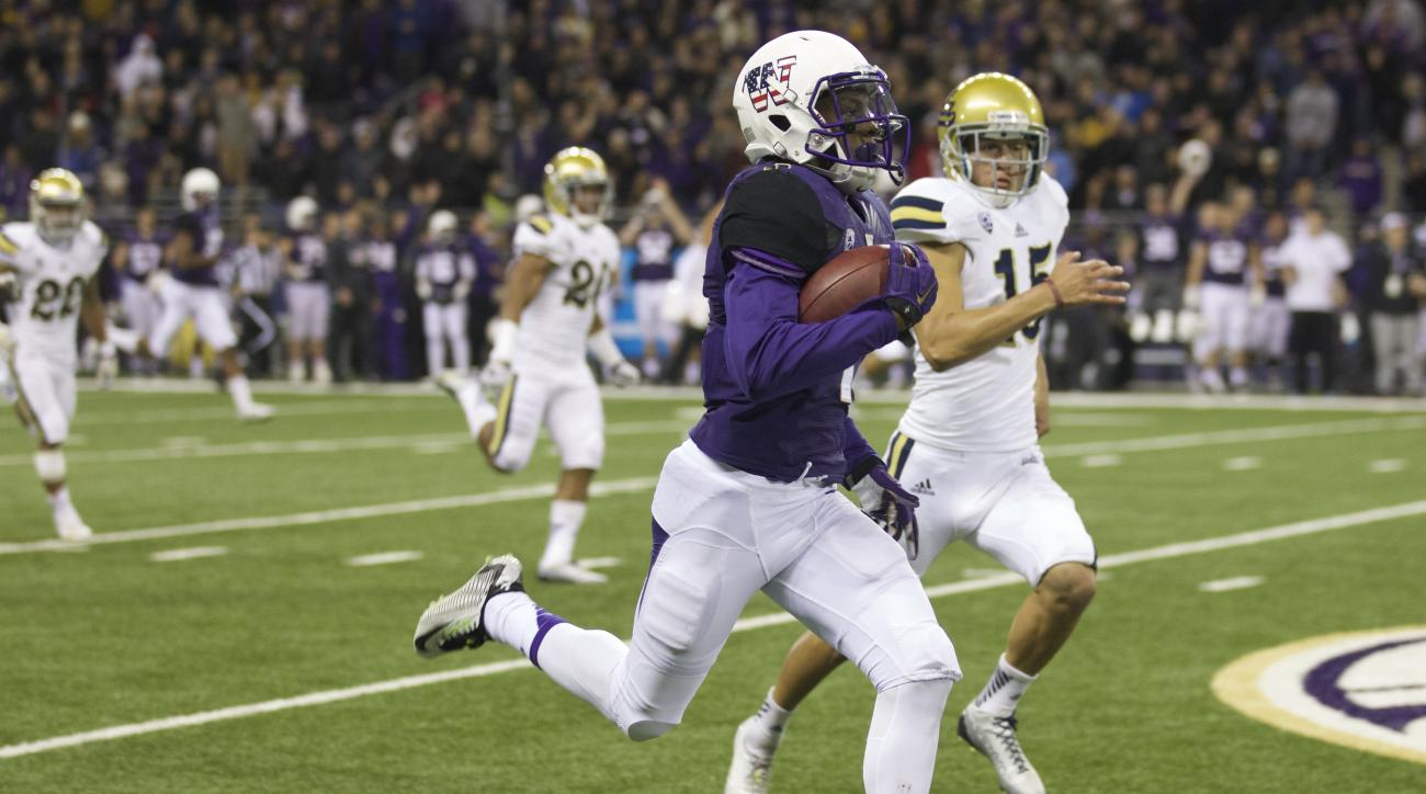 Washington returner John Ross III, foreground, returns a kickoff 100 yards for a touchdown in the second half of an NCAA college football game against UCLA, on Saturday, Nov. 8, 2014, in Seattle. UCLA won the game 44-30. (AP Photo/Stephen Brashear)