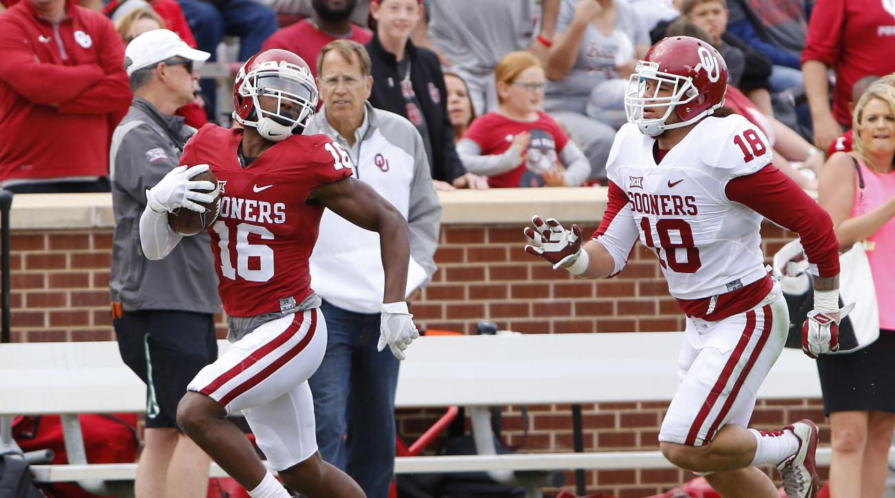 Oklahoma wide receiver Michiah Quick (16) runs ahead of Oklahoma's Curtis Bolton (18) for a touchdown during the Oklahoma spring NCAA college football game in Norman, Okla., Saturday, April 9, 2016. (AP Photo/Alonzo Adams)