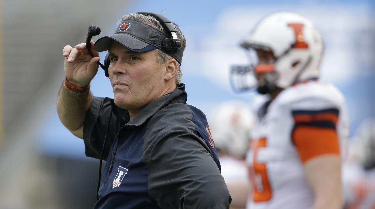 FILE - In this Dec. 26, 2014, file photo, former University of Illinois head coach Tim Beckman watches from the sidelines during an NCAA college football game in Dallas. The University of Illinois has announced a pair of settlements involving former femal