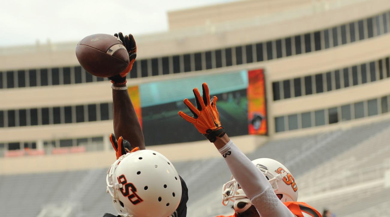 Oklahoma State black team corner back Darius Curry (2) deflects a goal line pass intended for orange team wide receiver Marcell Ateman during a spring NCAA college football game in Stillwater, Okla., Saturday, April 16, 2016. The Black team defeated  the