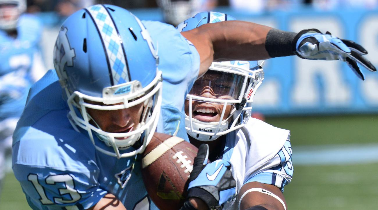 North Carolina's Mack Hollins (13) battles Corey Bell Jr., for a first down during the North Carolina Spring Football Game in Kenan Stadium, Saturday April 16, 2016, in Chapel Hill, N.C. (Bernard Thomas/The Herald-Sun via AP) MANDATORY CREDIT