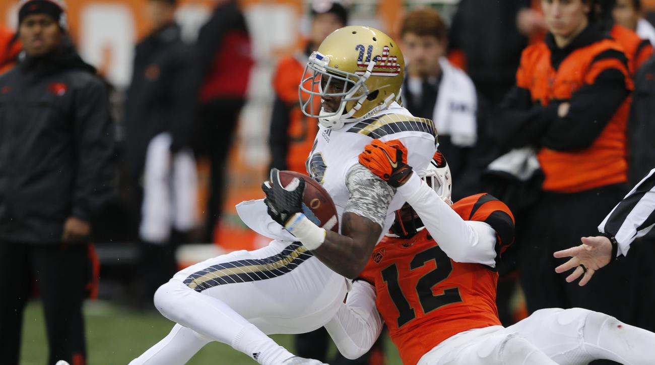 FILE - In this Nov. 7, 2015, file photo, UCLA's Kenneth Walker is tackled by Oregon State's Kendall Hill, right, after making a catch during an NCAA college football game in Corvallis, Ore. Walker is one potential option for UCLA coach Jim Mora, who is lo