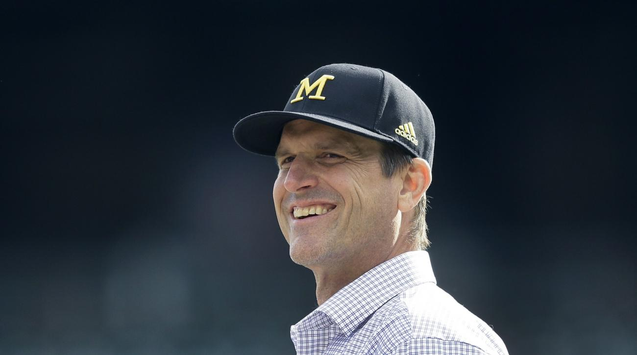 University of Michigan head football coach Jim Harbaugh watches batting practice before a baseball game between the Detroit Tigers and the Oakland Athletics, Wednesday, April 27, 2016, in Detroit. (AP Photo/Carlos Osorio)