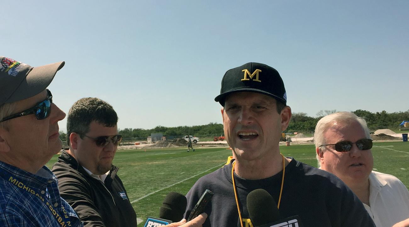 FILE - In this Feb. 29, 2016, file photo, University of Michigan NCAA college football head coach Jim Harbaugh speaks to reporters at IMG Academy in Bradenton, Fla. The NCAAs Division I Board of Directors has rescinded the ban on satellite camps. The boar