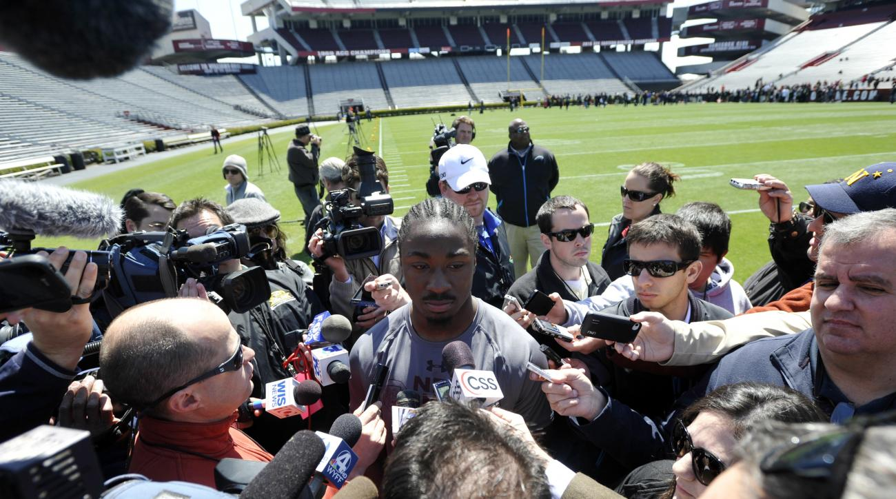 FILE - In this March 27, 2013 file photo, running back Marcus Lattimore, center, speaks with the media during South Carolina's NFL football pro day in Columbia, S.C. Three years ago, South Carolina's record-setting running back Marcus Lattimore waited anx