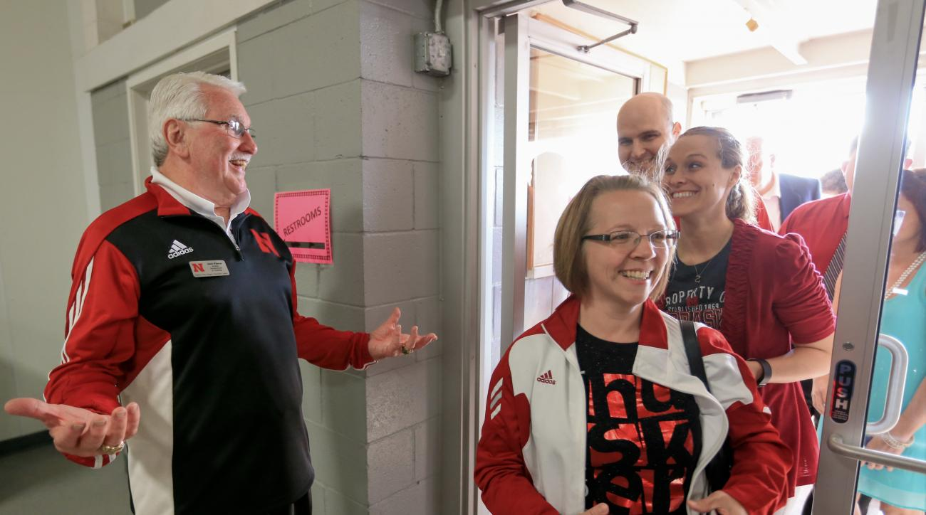In this May 11, 2016 photo, Nebraska development officer Jack Pierce, left, greets Husker fans arriving to see and hear NCAA college football head coach Mike Riley at the exhibition hall of the Platte County Agricultural Society in Columbus, Neb. In the b