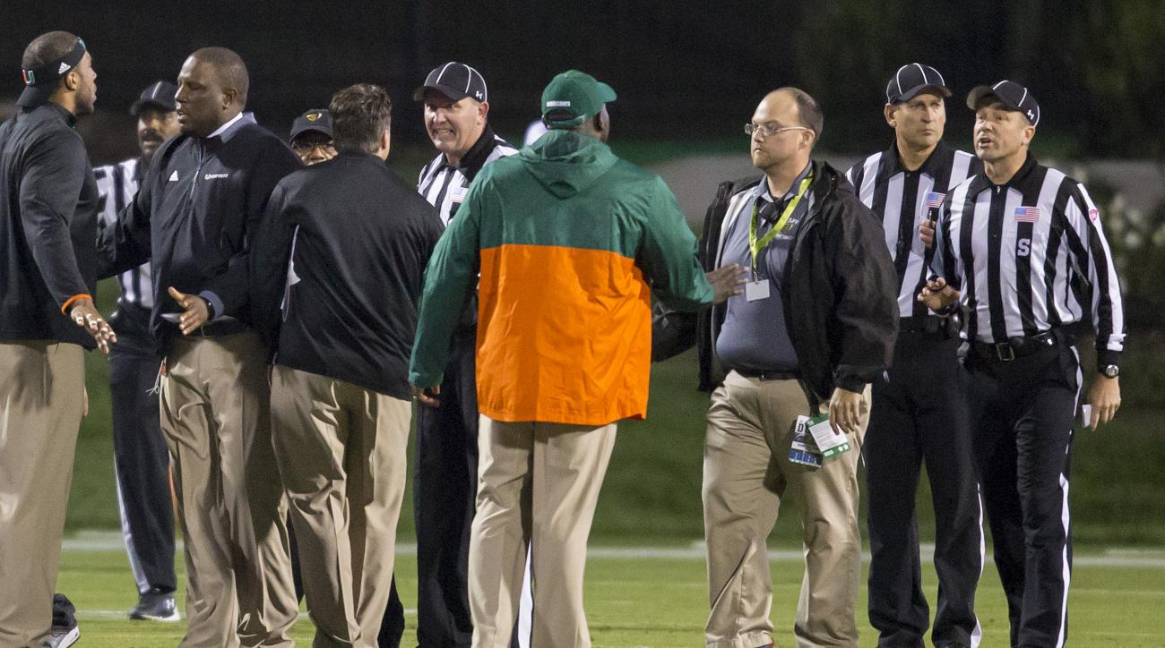 Miami coaches speak with officials on the field following a controversial kickoff return, with eight laterals, that ended in a touchdown to end the game and give Miami the win, 30-27, over Duke in an NCAA college football game, in Durham, N.C., Saturday,