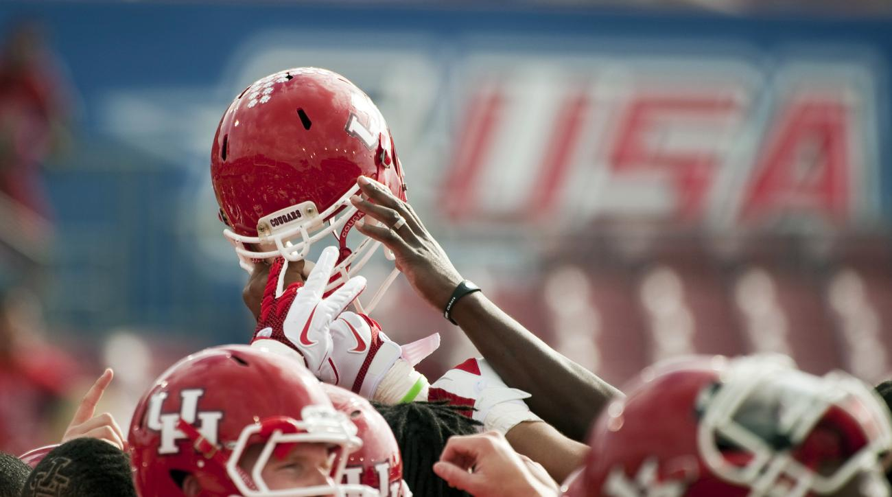 FILE - In this Dec. 3, 2011, file photo, Houston players gather before a Conference USA championship NCAA college football game against Southern Mississippi in Houston. Conference USA announced Wednesday, May 25, 2016, that it has reached a multiyear agre
