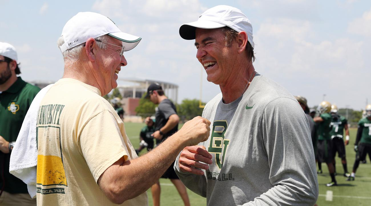 FILE - In this Aug. 5, 2014, file photo,Baylor University President Ken Starr, left, jokes with head football coach Art Briles, right, on the first day of NCAA college football practice in Waco, Texas. Baylor University's board of regents says it will fir