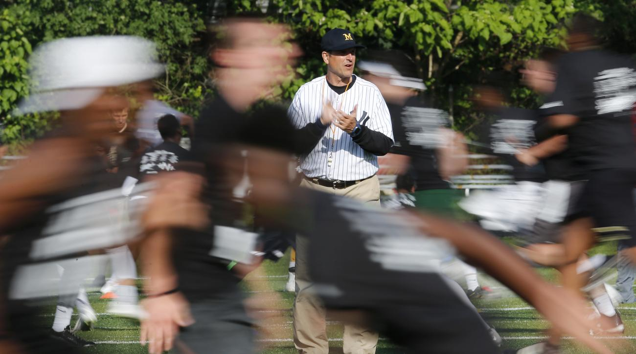 Michigan coach Jim Harbaugh, center, claps as high school athletes run drills during the Next Level Football Camp at Paramus Catholic High School, Wednesday, June 8, 2016, in Paramus, N.J. (AP Photo/Julio Cortez)