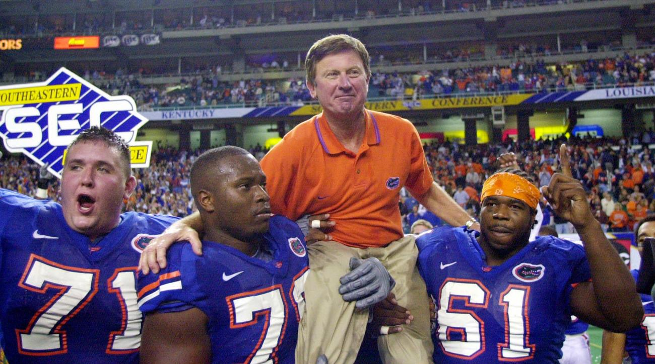 FILE - In this Dec. 2, 2000, file photo, Florida head coach Steve Spurrier is carried off the field  by Mike Pearson (71), Kenyatta Walker (78) and Gerard Warren (61) after the Gators downed Auburn 28-6 in the SEC Championship NCAA college football game a